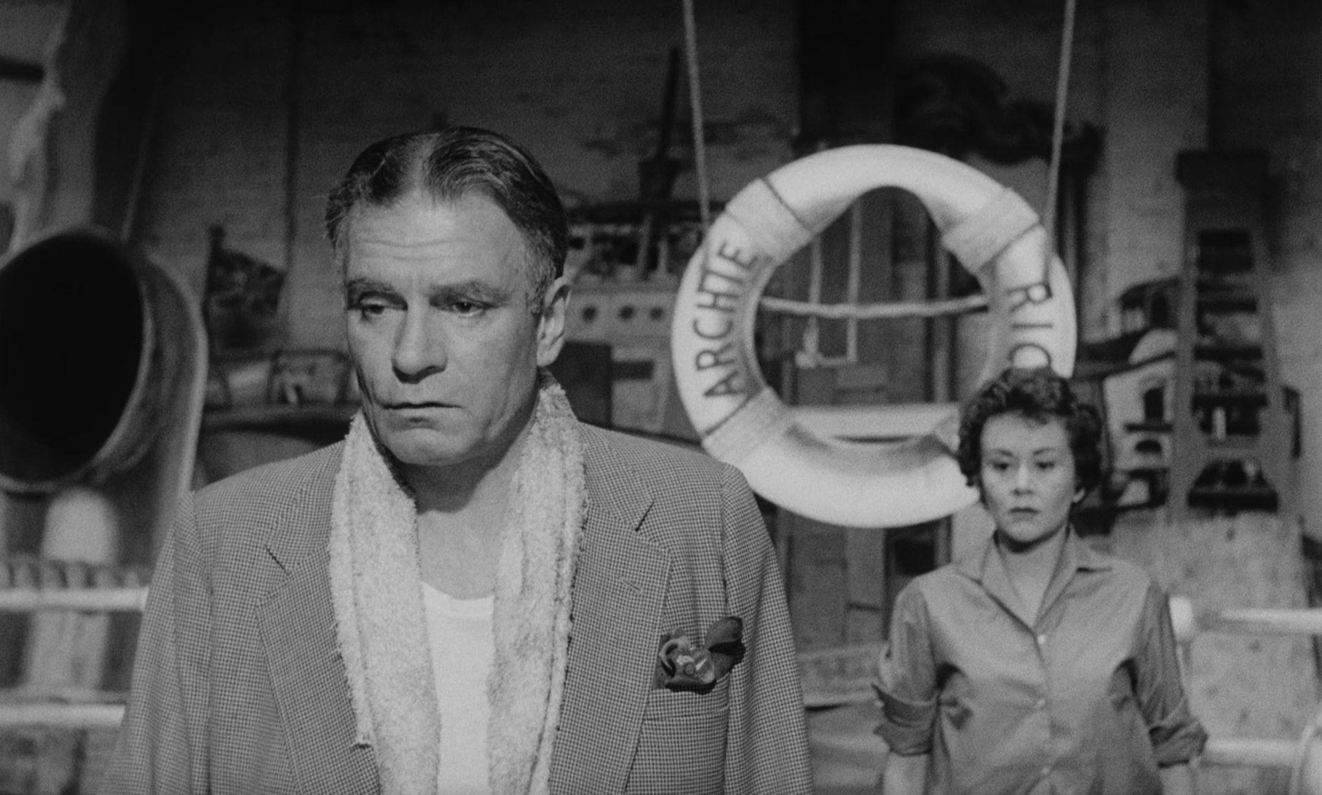 Laurence Olivier als Archie Rice hinter der Bühnemit traurigem Blick, im Hintergrund Joan Plowright als Rices Tochter Jean.