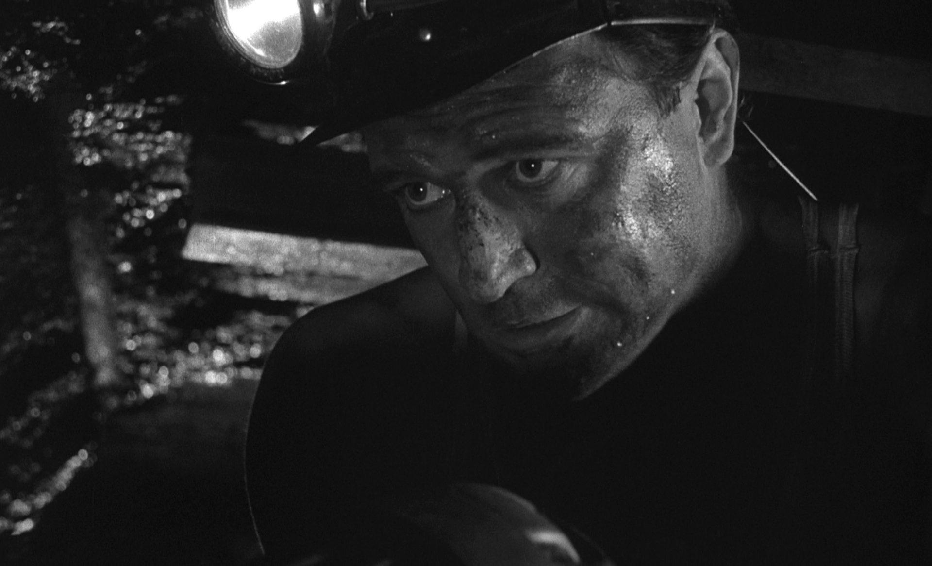 Nahaufnahme von Richard Harris als Frank Machin als Bergarbeiter bei der Arbeit im dunklen Stollen.