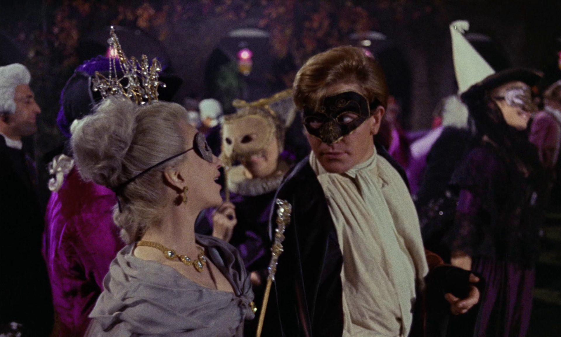 Tom Jones maskiert mit einer ebenfalls maskierten Dame im Trubel eines Maskenballs.