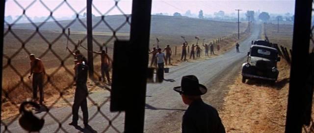 Häftlinge arbeiten unter Bewachung an einer Straße, Copyright: Warner
