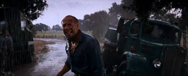 George Kennedy als Häftling im strömenden Regen