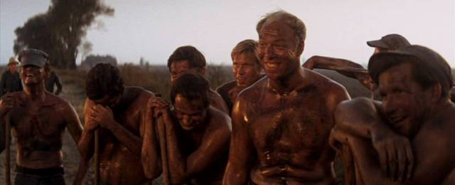 eine Reihe nassgeschwitzter Häftlinge steht am Straßenrand