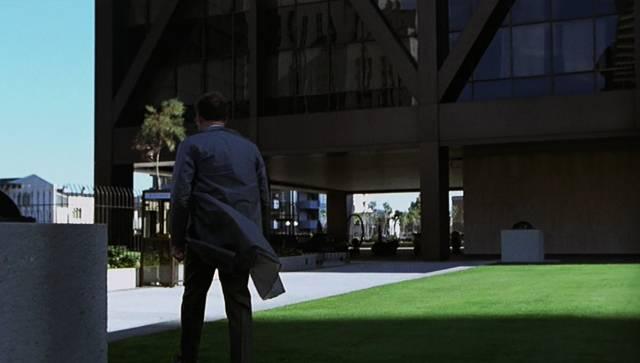 Harry Caul wandelt entlang des One Maritime Plaza, einem Hochhaus mit Glasfassade im Bankenviertel von San Francisco
