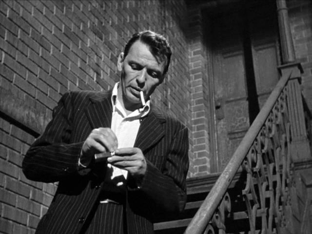 Frank Sinatra als Frankie Machine, der sich an einer Treppe eine Zigarette anzündet