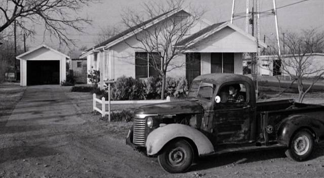 ein Kleintransporter parkt vor einem der Holzhäuser