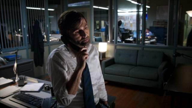 David Tennant als Detective Emmett Carver am Telefon in seinem Büro