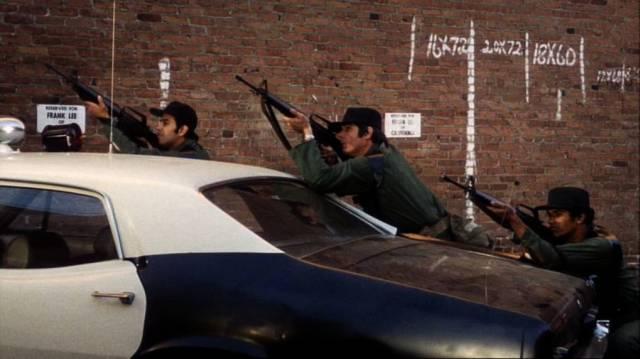 mit Maschinengewehren bewaffnete Polizisten in Deckung hinter einem Polizeiwagen, Copyright: Paramount