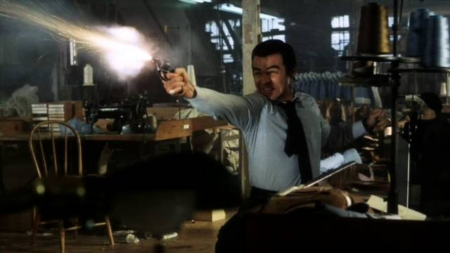 Burt Reynolds feuert in einer Fabrikhalle einen Schuss ab