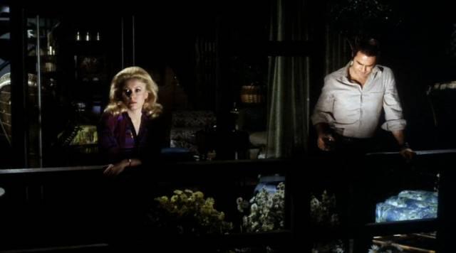 Catherine Deneuve und Burt Reynolds lehnen in der Dunkelheit am Rand ihres Balkons