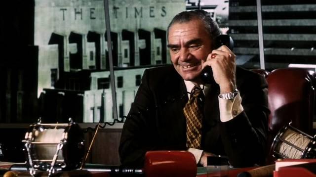 Ernest Borgnine als Santoro mit Telefonhörer am Schreibtisch