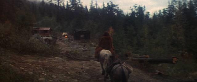 McCabe reitet auf einem Pferd einem Lagerfeuer entgegen