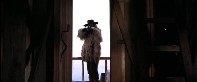 ein Auftragskiller steht mit seinem Gewehr im Anschlag im Eingang einer Hütte