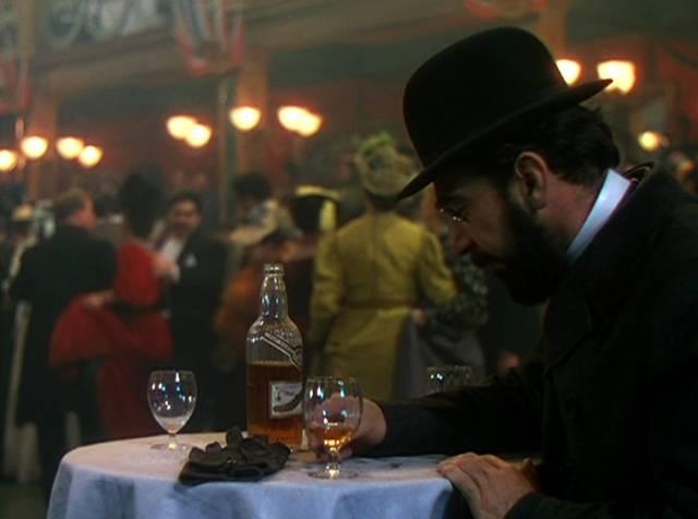 """José Ferrer in der Rolle des Künstlers Henri de Toulouse-Lautrec sitzt mit seinem Cognac an einem Tisch im """"Moulin Rouge"""" und zeichnet"""