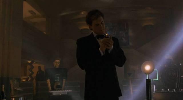 Mark Moses steht in einem dunklen Raum und zündet sich eine Zigarette an