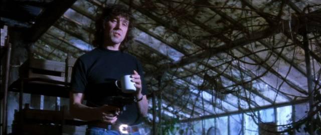 Stephen Rea als IRA-Terrorist Fergus, der mit gezogener Waffe und einer Kaffeetasse im verlassenen Gewächshaus steht