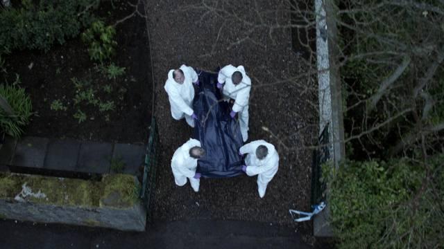 eine zugedeckte Leiche wird vom Tatort weggetragen