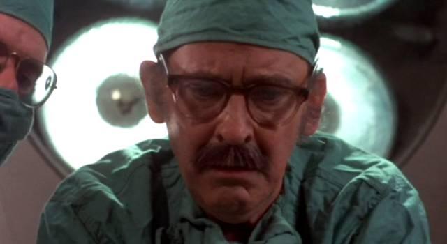 ein Arzt blickt während der Operation von oben auf den Patienten, Copyright: Simcha Productions
