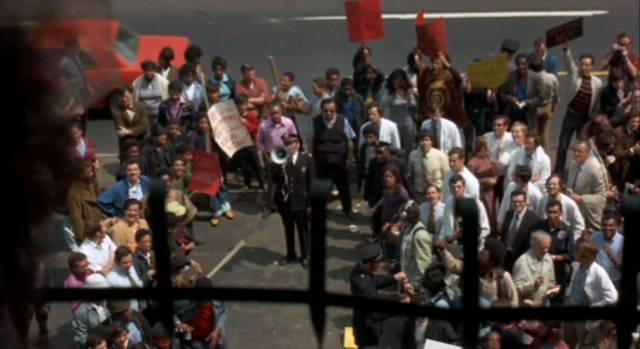 eine Demonstration protestierender Menschen vor dem Klinikgebäude, Copyright: Simcha Productions