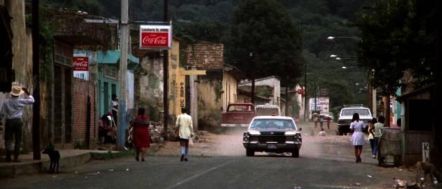 eine schwere Limousine fährt auf einer staubigen Straße in einer mexikanischen Kleinstadt