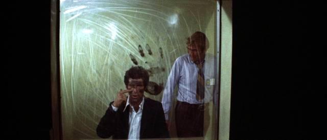Marlowe hinter einer verkratzten Scheibe im Verhörraum der Polizei, Copyright: MGM