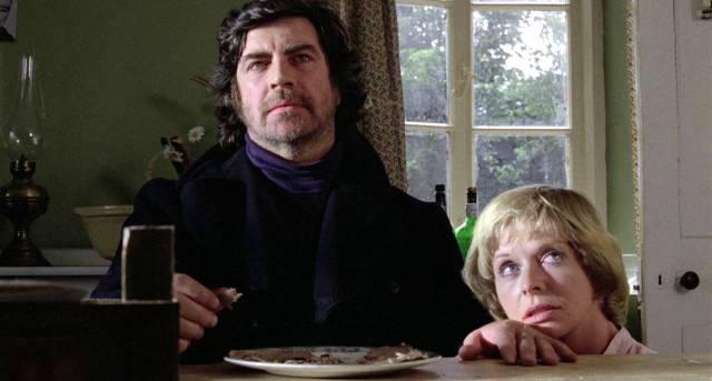 Alan Bates sitzt als Crossley am Esstisch, Susannah York liebkost in devoter Haltung als Rachel Fielding seine Hand