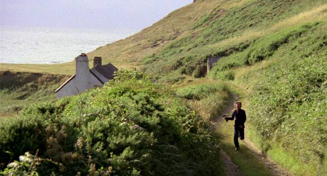 John Hurt rennt als Anthony Fielding auf einem Feldweg durch die Küstenlandschaft an einem kleinen Haus vorbei