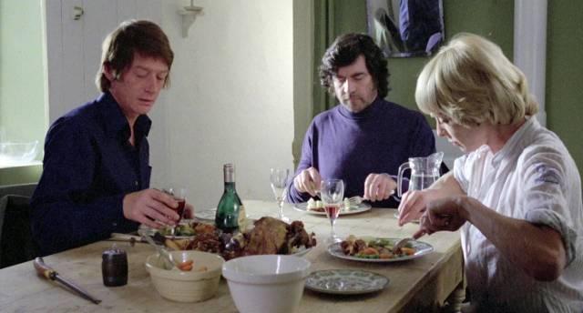 John Hurt, Alan Bates und Susannah York bei der gemeinsamen Mahlzeit am Esstisch