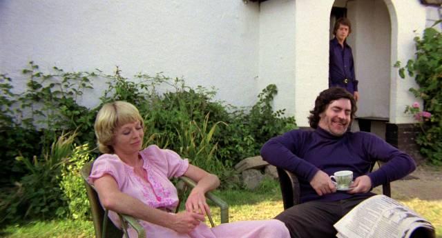 Susannah York und Alan Bates sitzen im Garten, während John Hurt im Hintergrund in der Tür lehnt