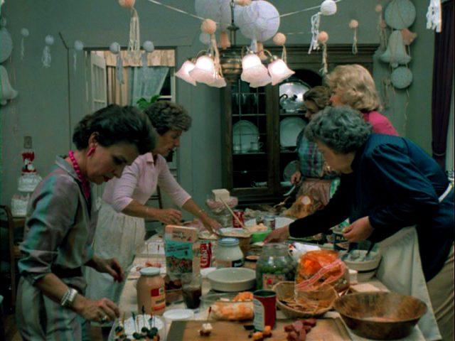 eine Gruppe Nachbarinnen bereitet Essen am Tisch der McKenzies zu