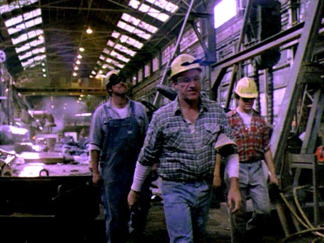 Harry (Gene Hackman) läuft mit Kollegen durch das Stahlwerk