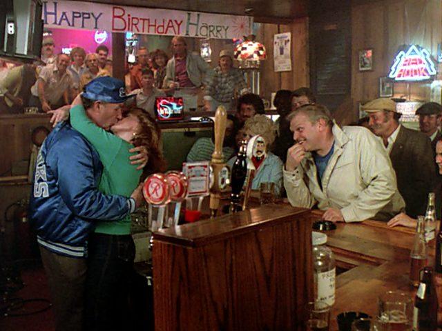 Harry (Gene Hackman) und Audrey (Ann-Margret) küssen sich an der Bar, während Nick (Brian Dennehy) mit einem Lächeln zusieht, Copyright: The Yorkin Company