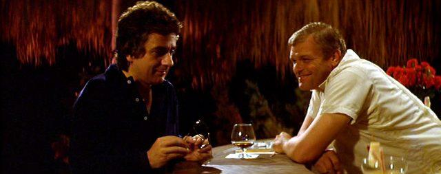 George (Dudley Moore) unterhält sich im mexikanischen Hotel mit dem Barkeeper Donald (Brian Dennehy)