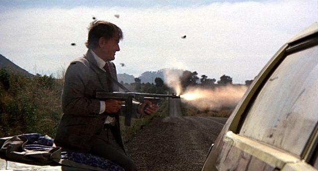 Quill (Gig Young) feuert eine Maschinenpistole ab