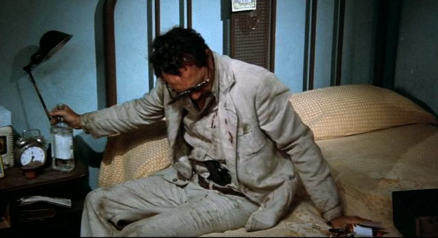 Bennie (Warren Oates) sitzt auf seinem Bett und umklammert mit einer Hand eine Schnapsflasche