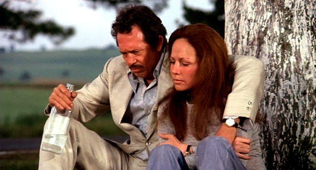 Bennie (Warren Oates) und Eliat (Isela Vega) sitzen mit einer Schnapsflasche an einem Baum
