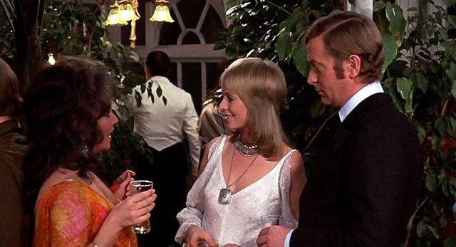 Zee und Robert Blakeley (Elizabeth Taylor und Michael Caine) im Gespräch mit Stella (Susannah York) auf einer Party, Copyright: Columbia Pictures