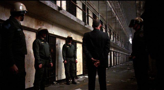 Warden Ranken (JohnP. Ryan) steht in Begleitung mehrerer Wachen im Zellentrakt, Copyright: Cannon Films