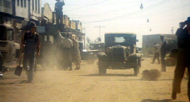 eine Limousine fährt auf einer staubigen Straße eines kleinen Orts