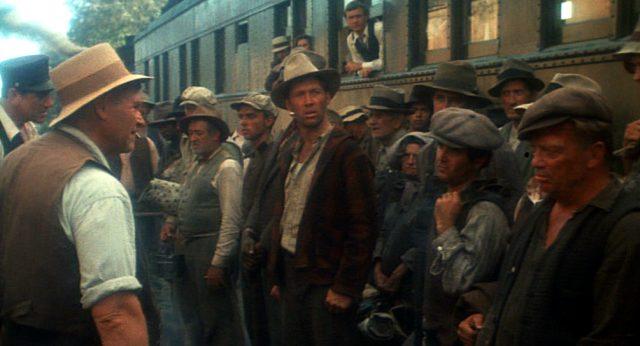 Woody Guthrie (David Carradine) steht in einer Gruppe vor einem Eisenbahnwaggon