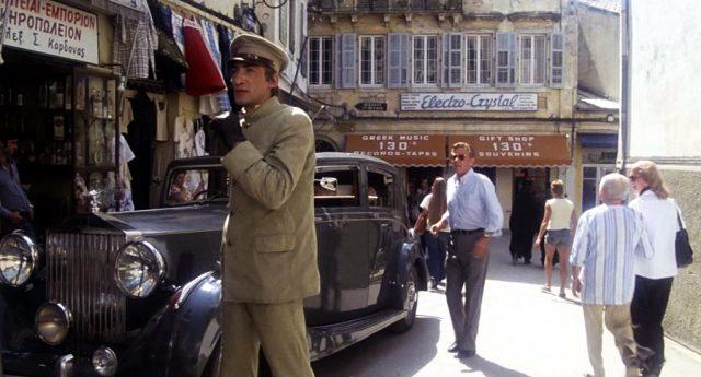 Chauffeur Kritos (Gottfried John) und Barry Detweiler (William Holden) vor einem Laden auf Korfu