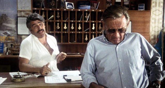 der griechische Hotelmanager (Mario Adorf) spricht an der Rezeption mit Barry Detweiler (William Holden)