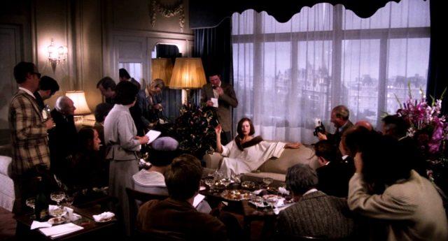 Fedora (Marthe Keller) auf einem Sofa in ihrer Hotelsuite, umgeben von Journalisten