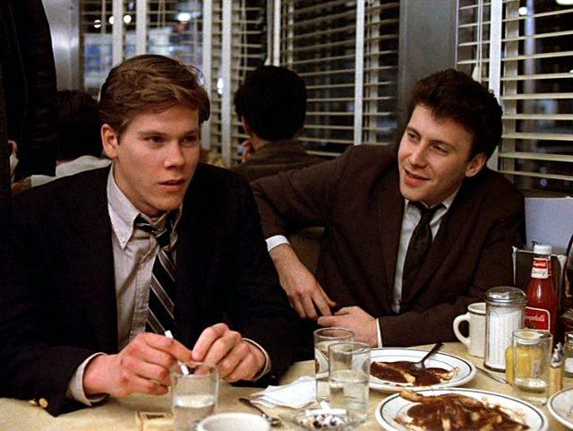 Timothy Fenwick (Kevin Bacon) und Modell (Paul Reiser) im Diner an einem Tisch voller Essen und Getränke