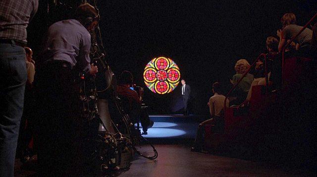 im Vordergrund die Studiokamera, im Hintergrund Howard Beale (Peter Finch) auf seiner Bühne