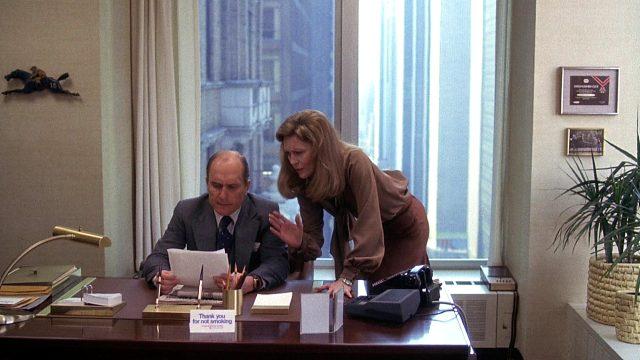 Diana Christensen (Faye Dunaway) im Gespräch mit Frank Hackett (Robert Duvall) an dessen Schreibtisch, Copyright: Turner Entertainment