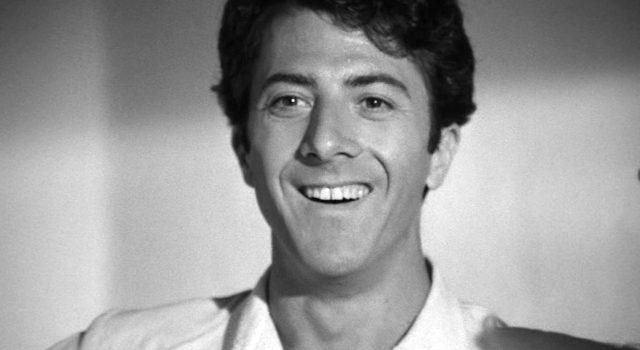 Close-up des jungen Lenny Bruce (Dustin Hoffman) mit breitem Lächeln