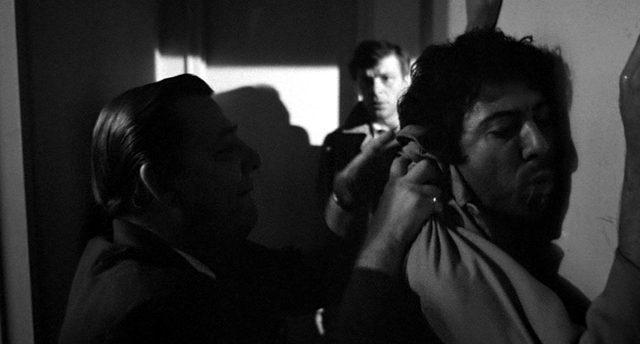 Lenny Bruce (Dustin Hoffman) wird von einem Mann an die Wand gedrückt