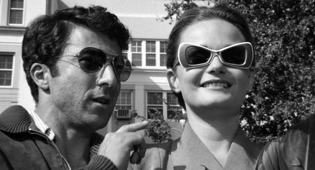 Lenny und Honey Bruce (Dustin Hoffman und Valerie Perrine) mit Sonnenbrillen vor einem Gebäude