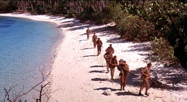 der Kommandotrupp marschiert am Rande des Dschungels einen Strand entlang