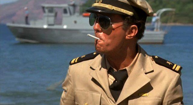 Cliff Robertson als Lieutenant Sam Lawson mit Sonnenbrille und Zigarette an einem Strand